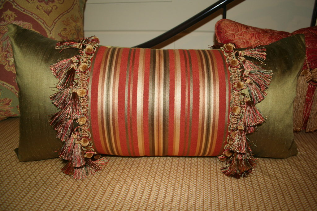 Closeup of neckroll, pillows, bedding, valances, shutters
