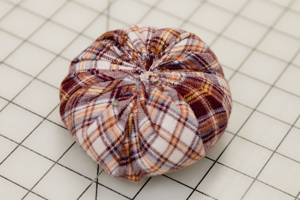 fabric pumpkin without a stem sitting on a craft mat