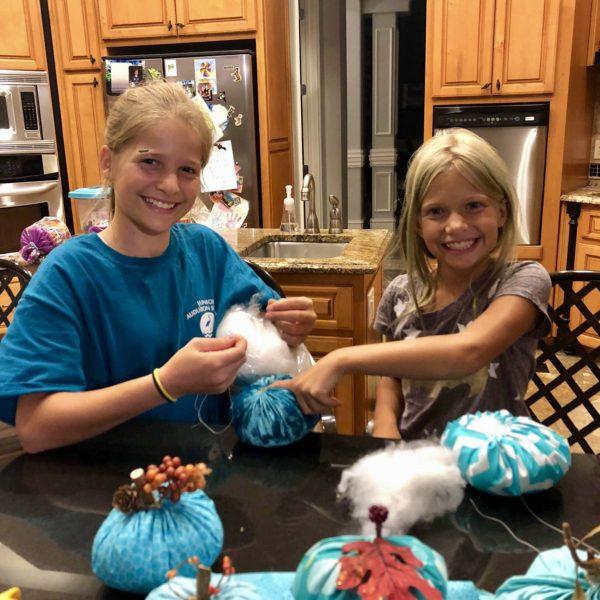 Julie and Emma sewing the teal pumpkins