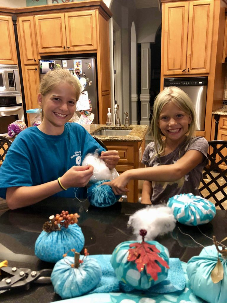 Julie and Emma sewing the teal pumpkins