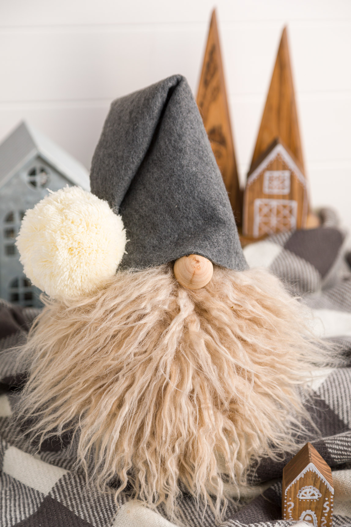 DIY Gnome with a faux fur beard and gray felt hat. Sitting on a gray and while buffalo check throw blanket.
