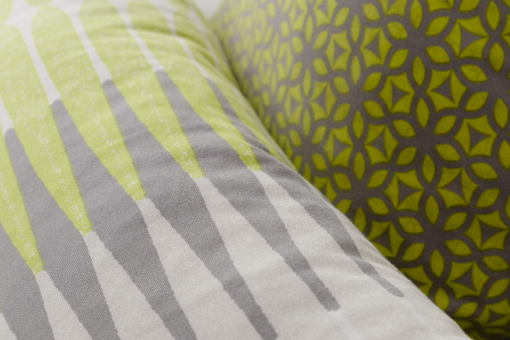 Fun geometric patterned DIY pillows, mix up the patterns and colors in the modern boys bedroom makeover