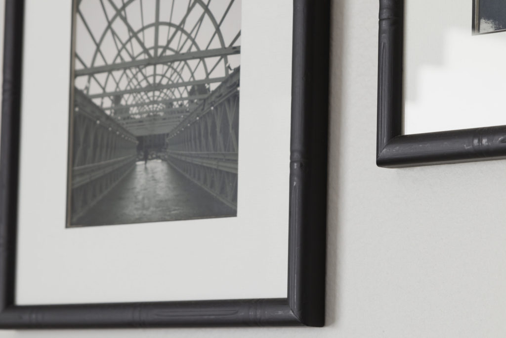 Painted thrift store frames, black and white photos taken on vacations add a personal touch to the modern boys room DIY makeover