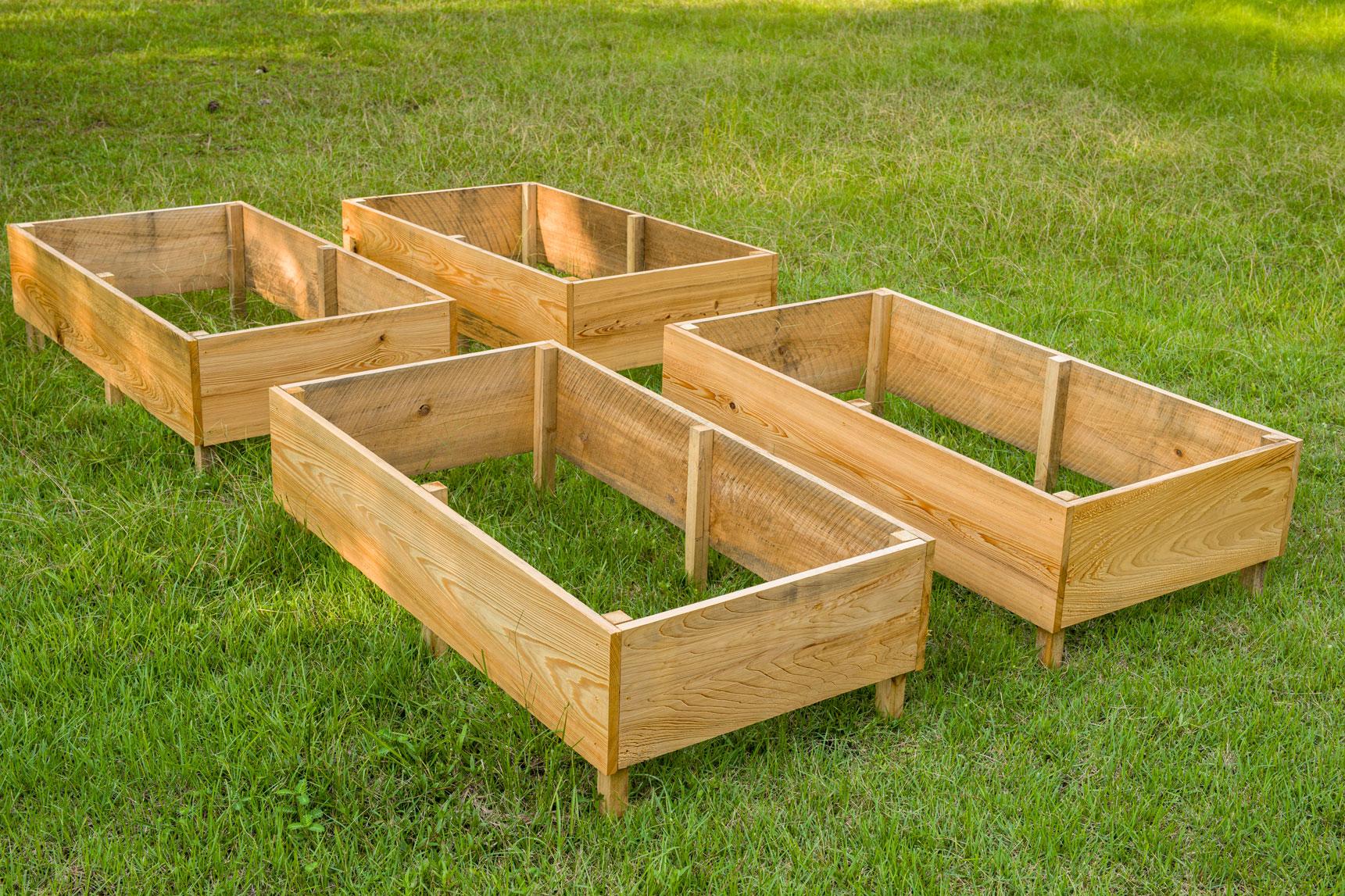 four DIY Raised Garden Beds sitting in the grass