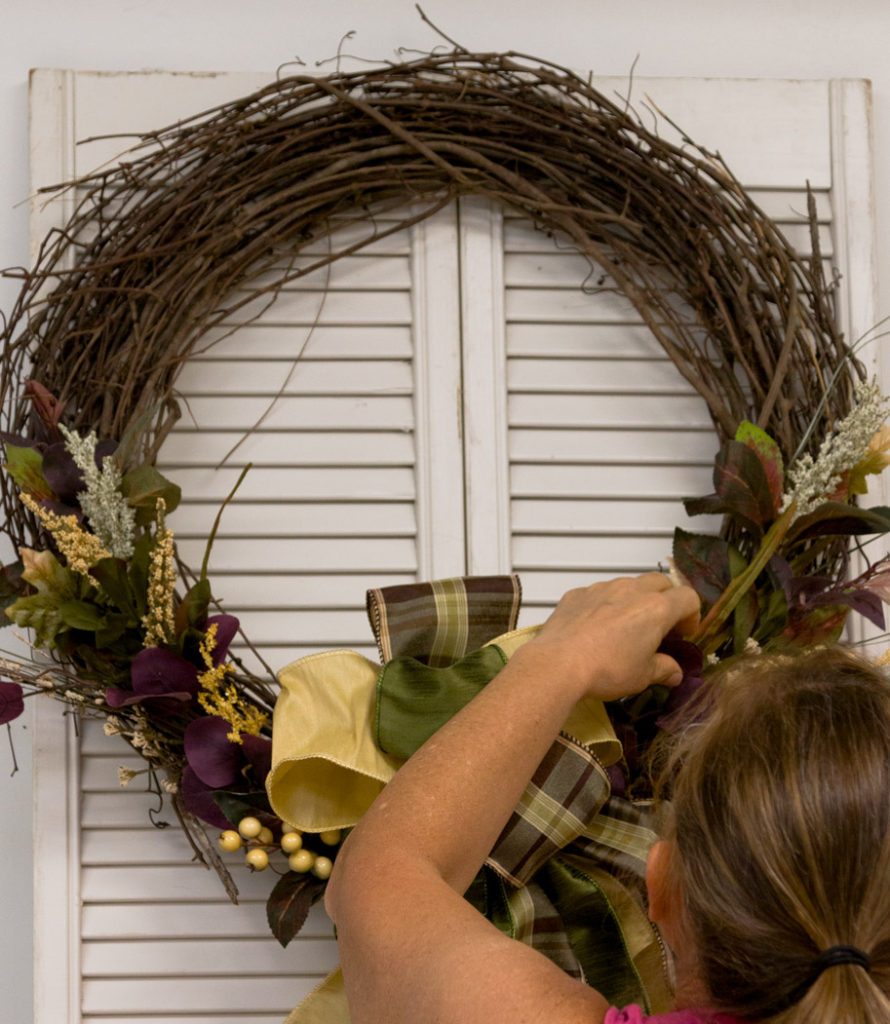 Adjusting the floral and bow on finished wreath
