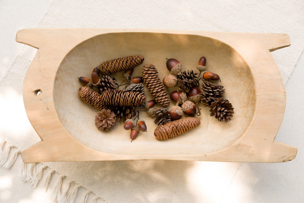 Vintage dough bowl with pine cones and acorns