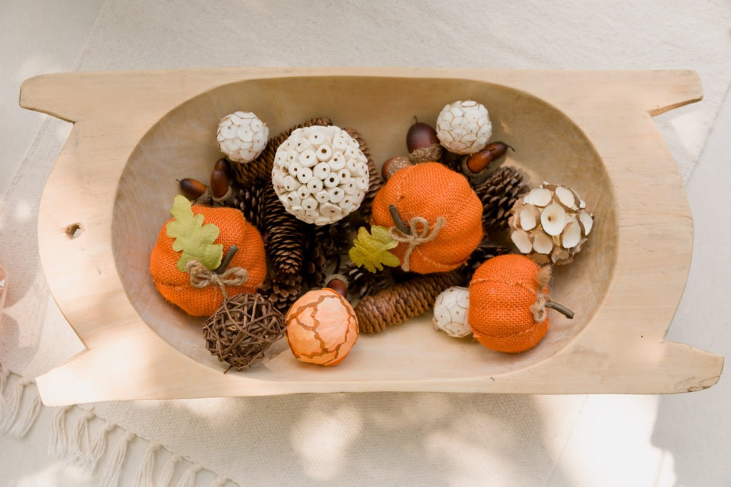 Vintage dough bowl with interesting round elements, pine cones, acrons and burlap pumpkins