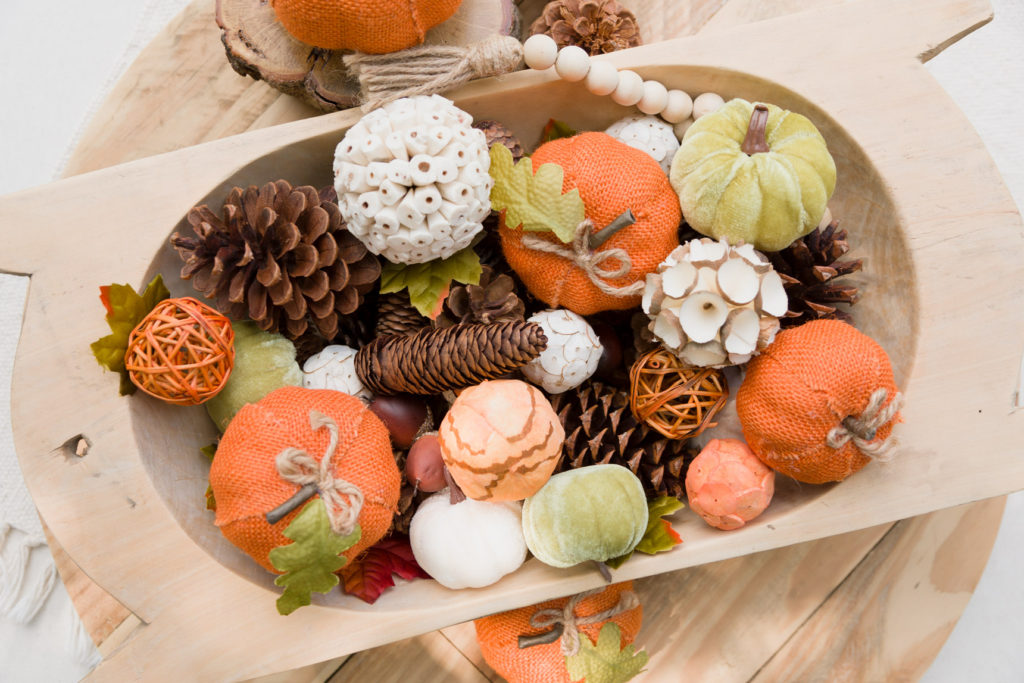 Finished dough bowl arrangement with natural elements, fabric pumpkins and wooden bead garland.