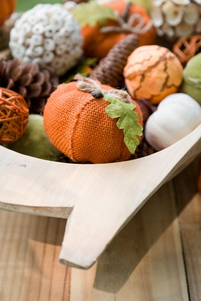 Dough bowl with fall vase fillers. Burlap pumpkins, acorns and pine cones.