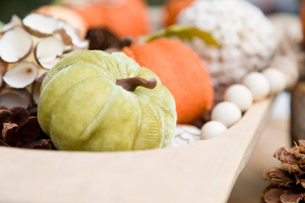 Velvet, burlap pumpkins mixed with organic elements in a vintage dough bow