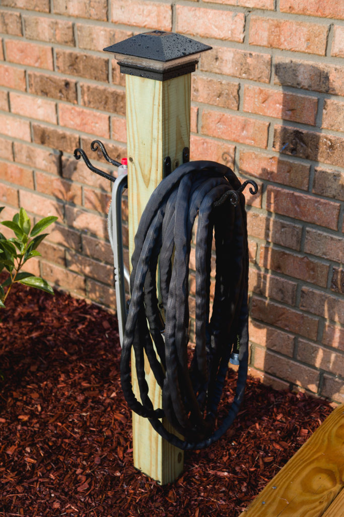 Closeup of completed garden hose storage post with solar light