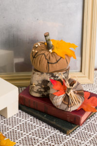 Cozy rustic decor with wood antique books and Goodwill skirt pumpkins