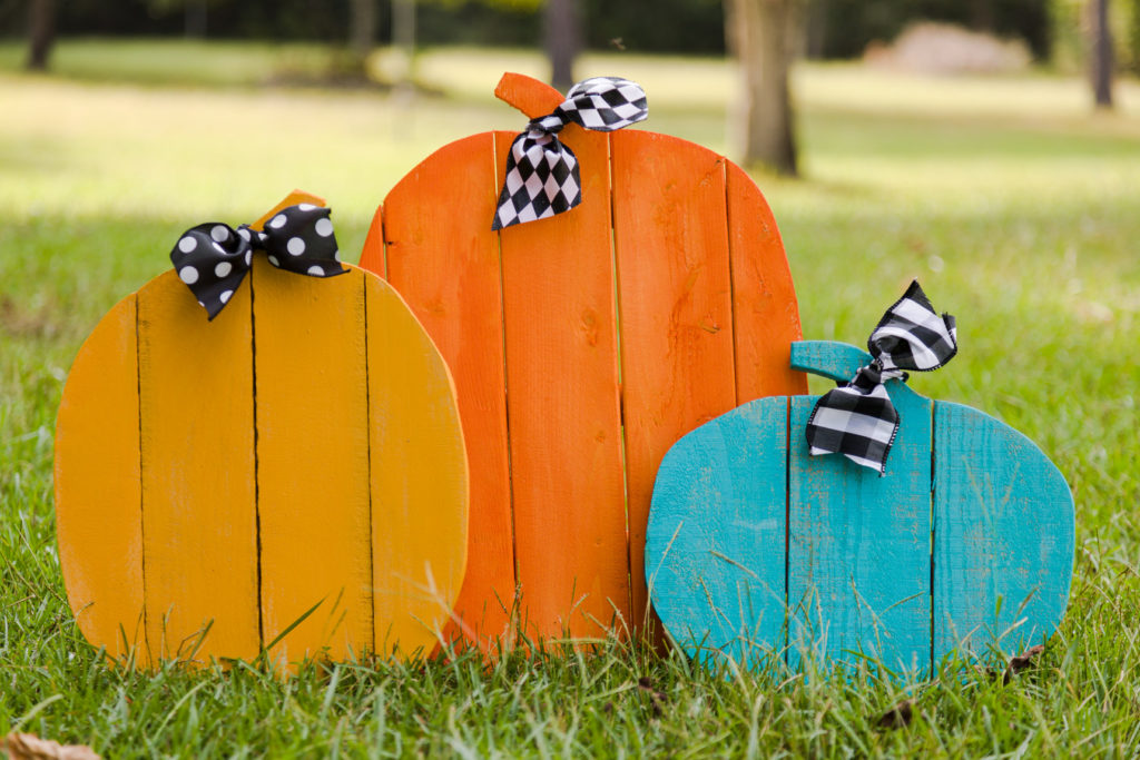 Orange, yellow and teal DIY rustic pallet pumpkins sitting in the grass