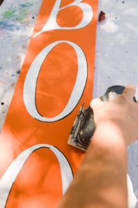 Sanding the orange Halloween sign