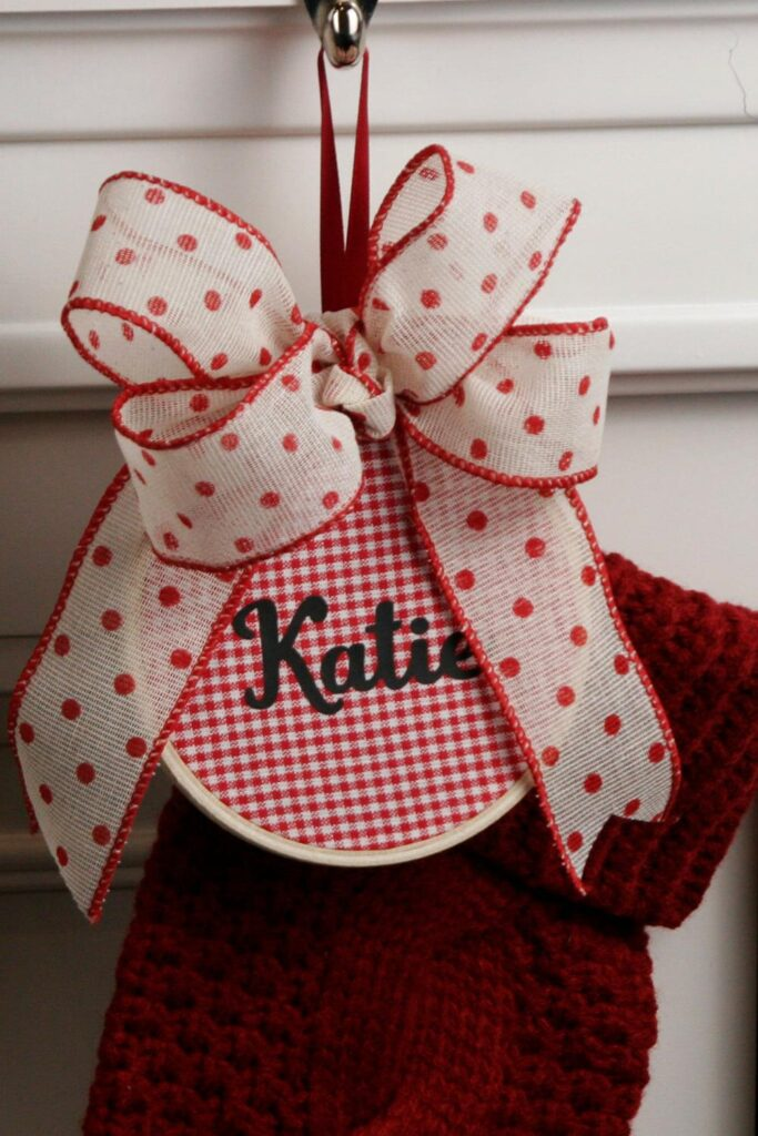 Embroidery hoop with red and white check fabric with the name Kate on it and a bow attached to a stocking