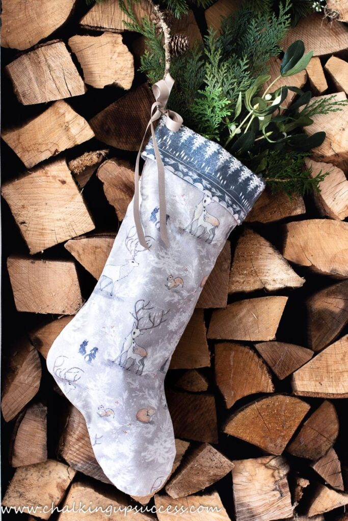 Tan and blue handmade stocking filled with greenery hanging from a stack of chopped wood