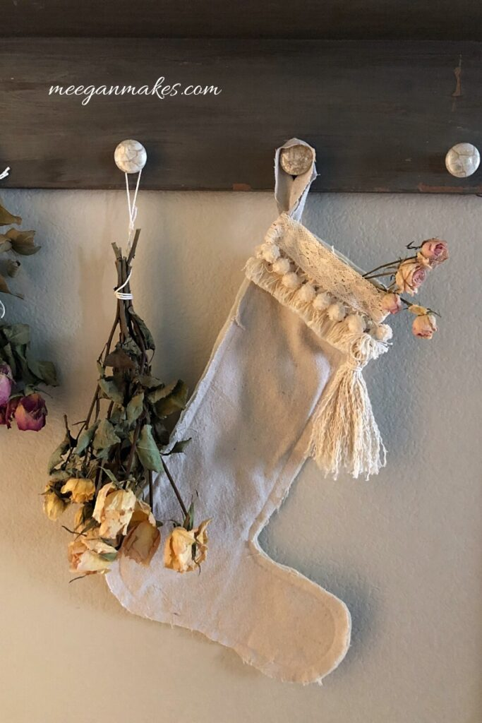 cream colored handmade stocking with trim hanging from a hook