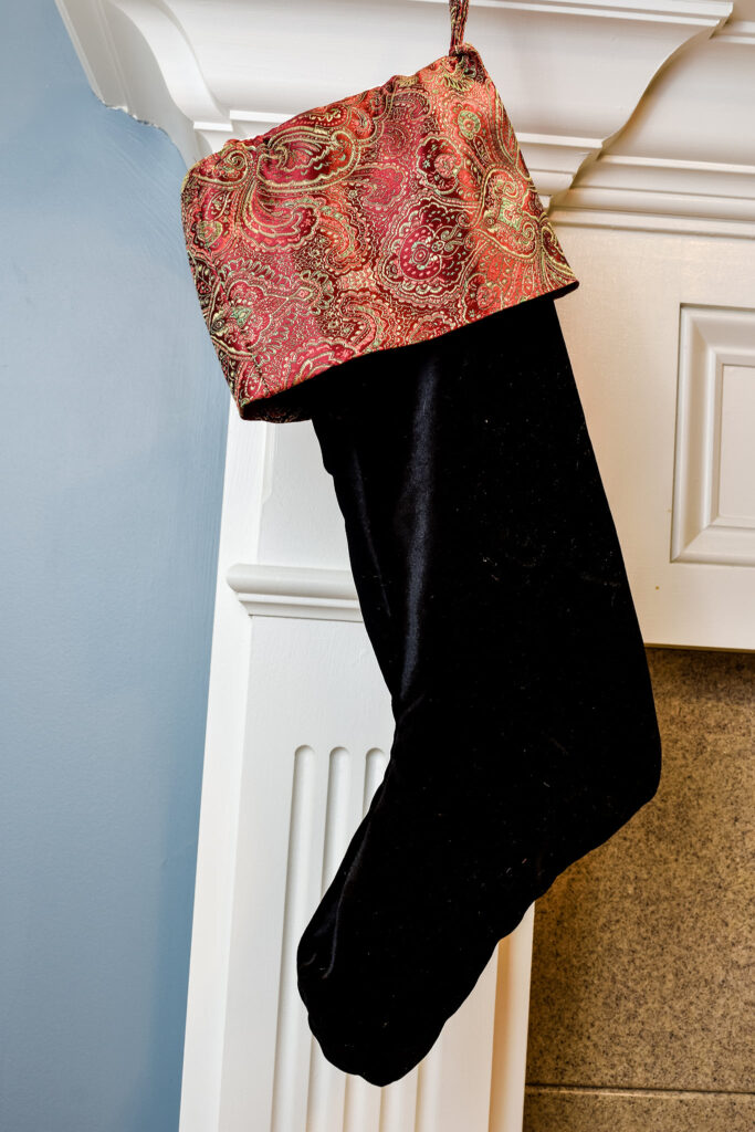 Velvet stocking with an jacquard cuff hanging from a fireplace mantel