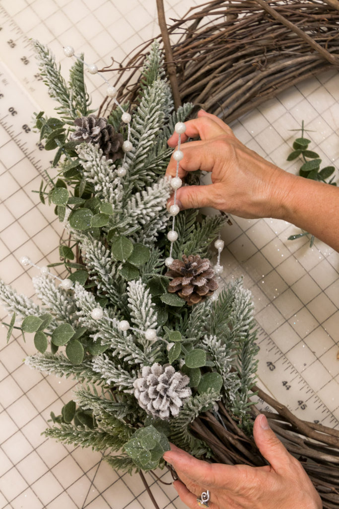 Filling in the wreath form with more floral picks