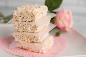 Rice Krispie Treats stacked on a pink dollie