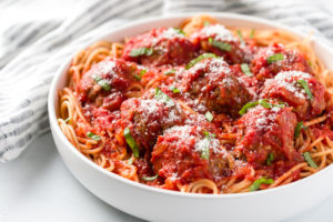 Marinara sauce over meatballs and spaghetti