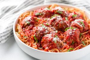 Marinara sauce over meatballs and spaghetti