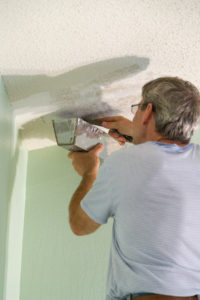 Scraping the popcorn ceiling off with a putty knife