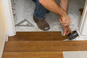 Using a rubber mallet to install flooring under the door jamb