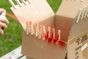 Spray painting the clothespins red