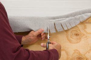 In the curved areas make relief cuts to make the fabric follow the contour of the headboard.