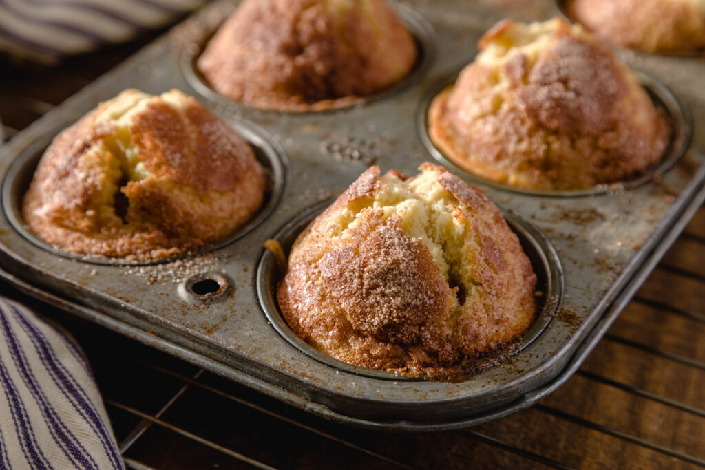 Tall muffins with sugar mixture bubbling out of the delicious golden peaks
