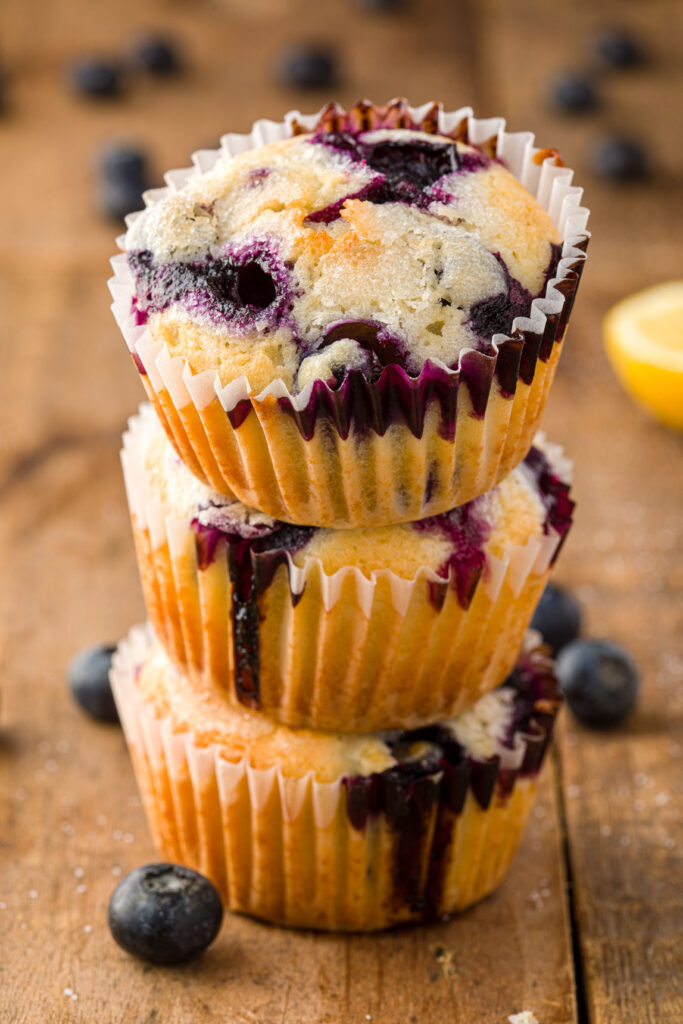 a stack of three lemon Blueberry muffins on a wood board