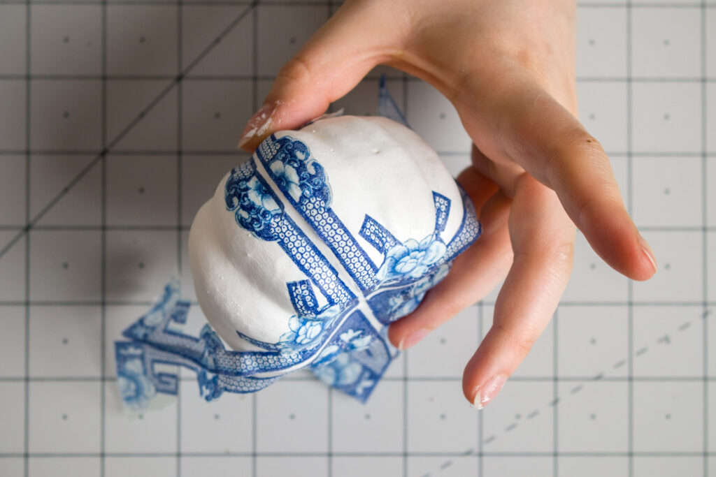Mod Podging napkin design to the pumpkin