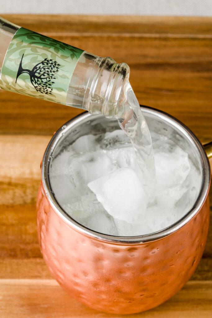 Fill copper cups with ginger beer