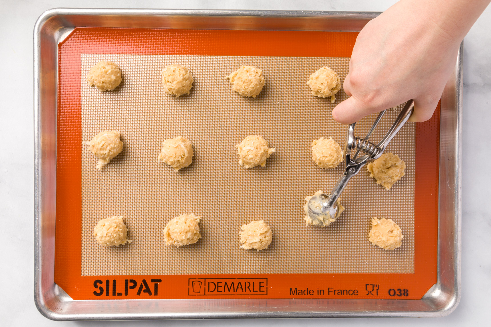 Drop coconut cookie dough onto a lined sheet pan