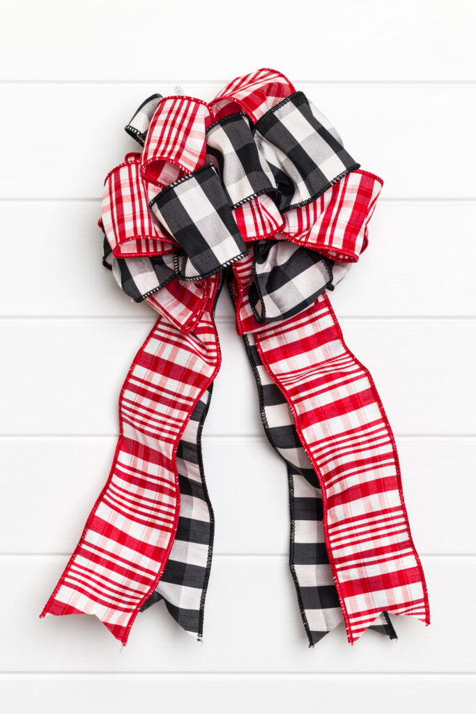 Double Ribbon Bow made of red, white and black ribbons bow with four ribbon tails sitting on a white table