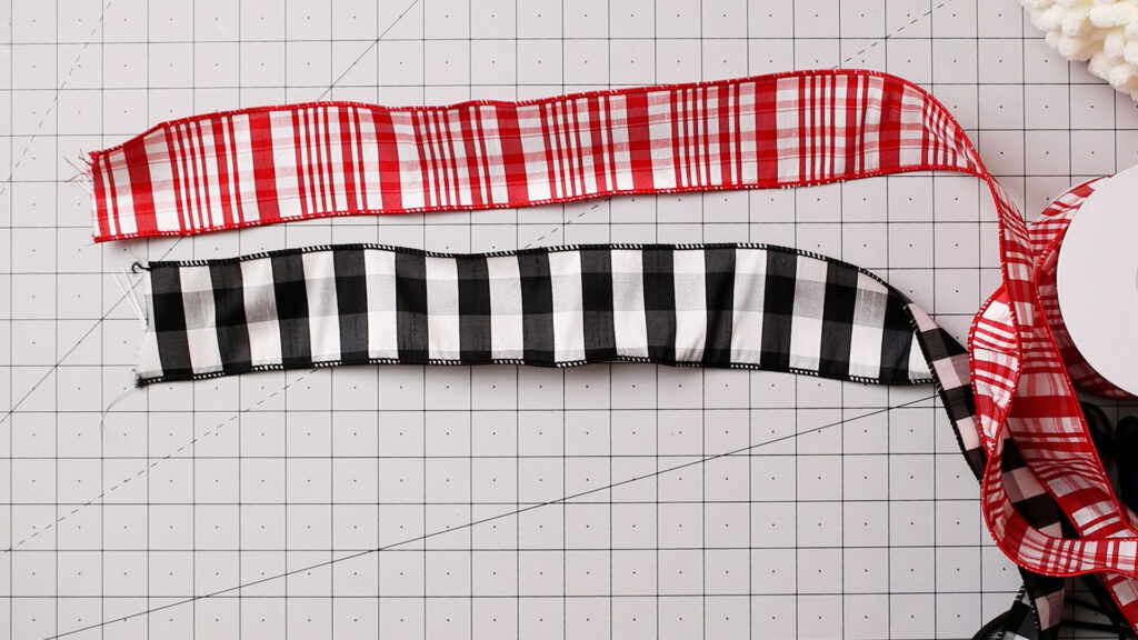Red and white plus black and white ribbon on a craft mat