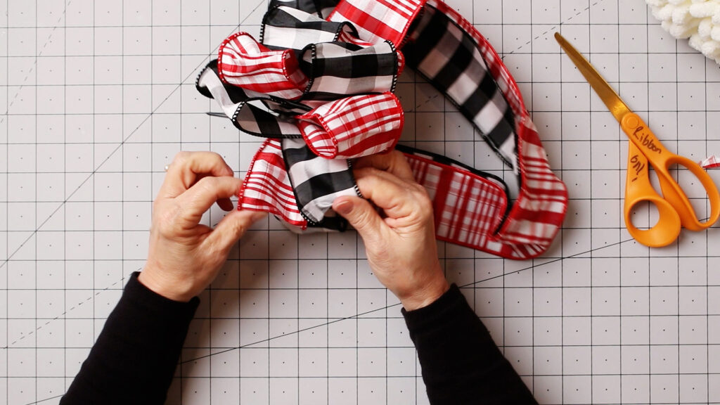 Fluffing the dupioni ribbon bow on craft mat