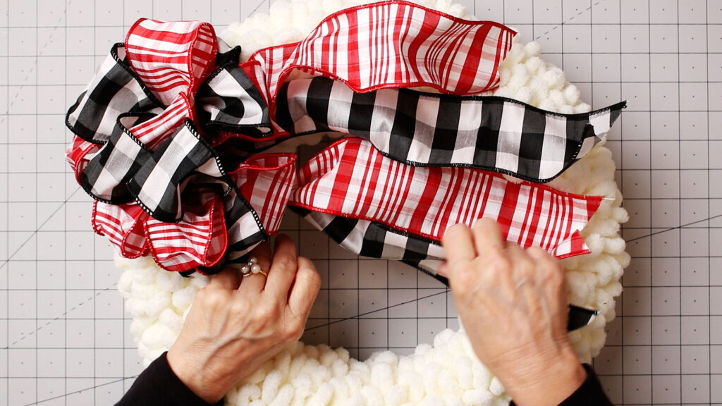 Attaching the bow to a white loopy yarn wreath