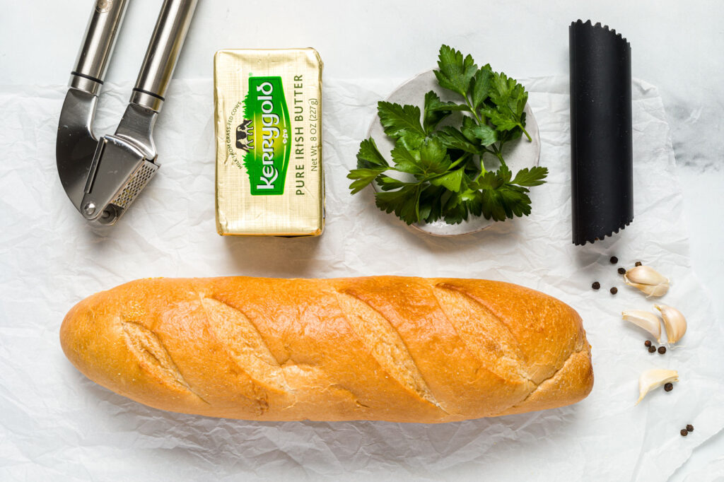 Bread, butter, garlic cloves, and parsley