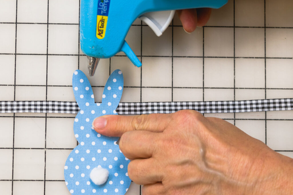 Glue the bunnies on the ribbon