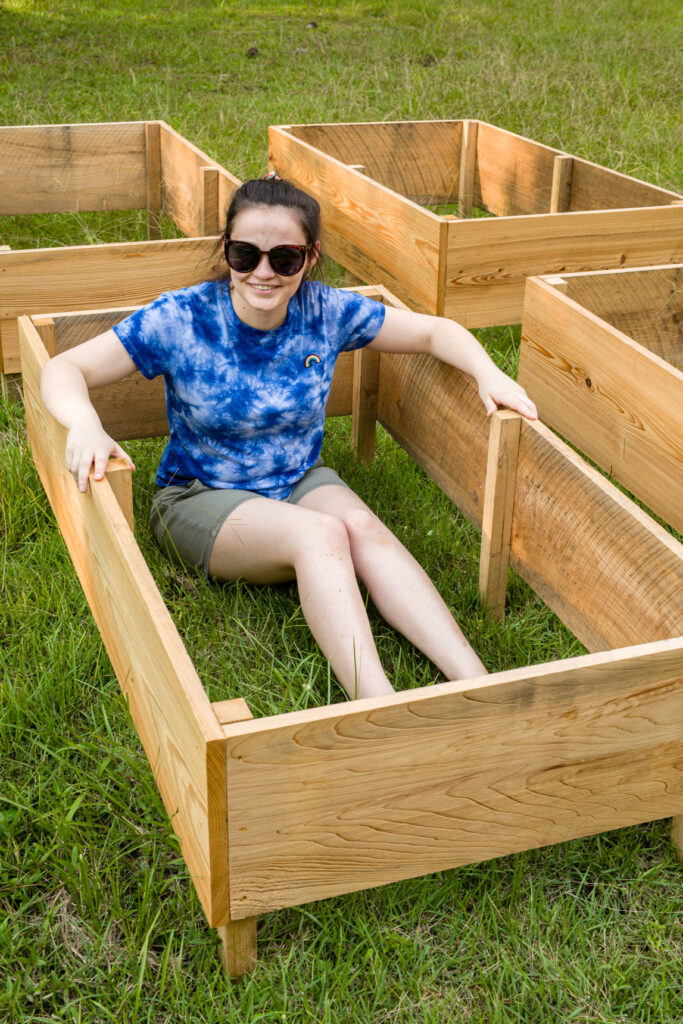 Girl sitting inside DIY wooden garden box on the grass