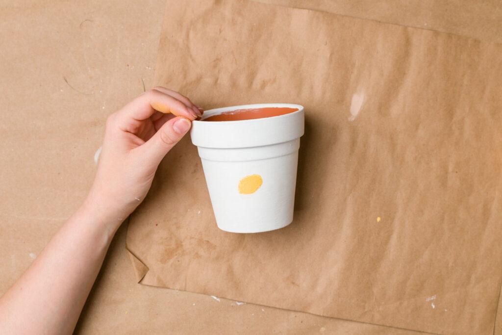 Yellow paint thumbprint on white painted terracotta pot