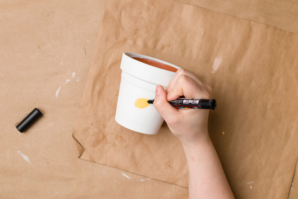 Drawing the bee on painted pot
