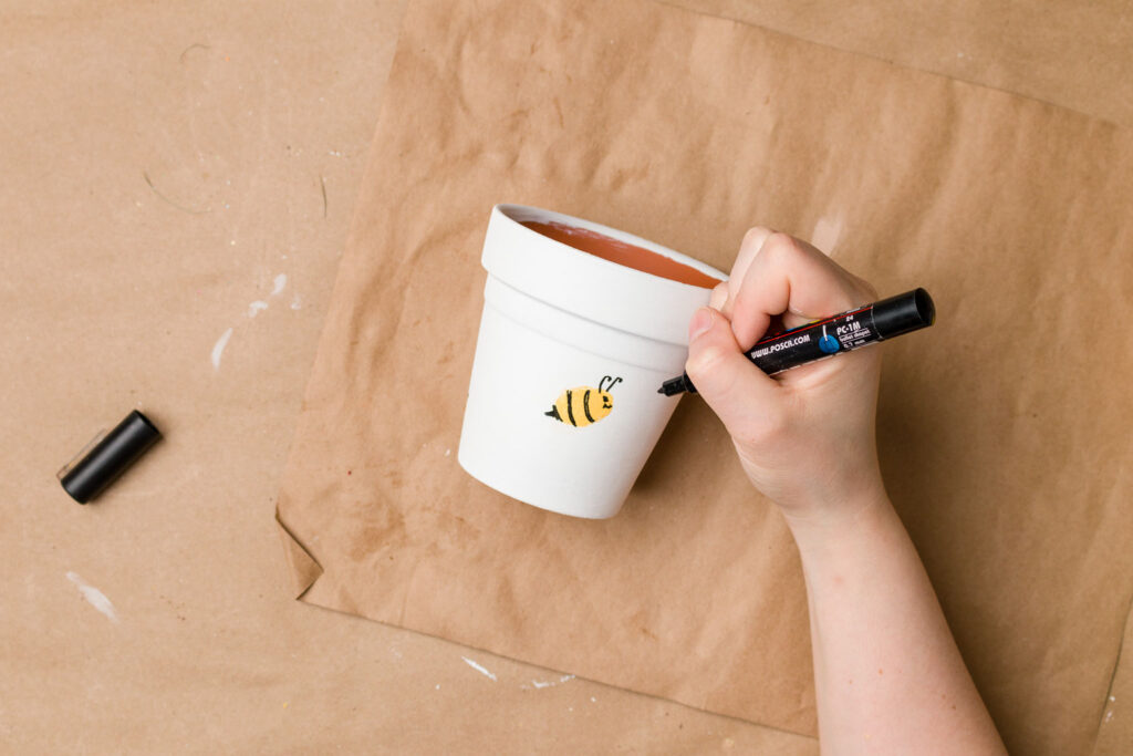 Drawing the antennae and tail on the thumbprint bee flower pot