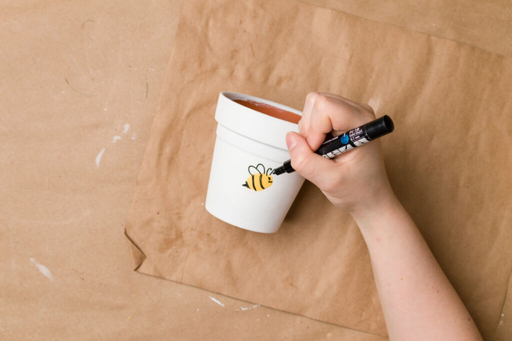 Painted flower pot with thumbprint bee face