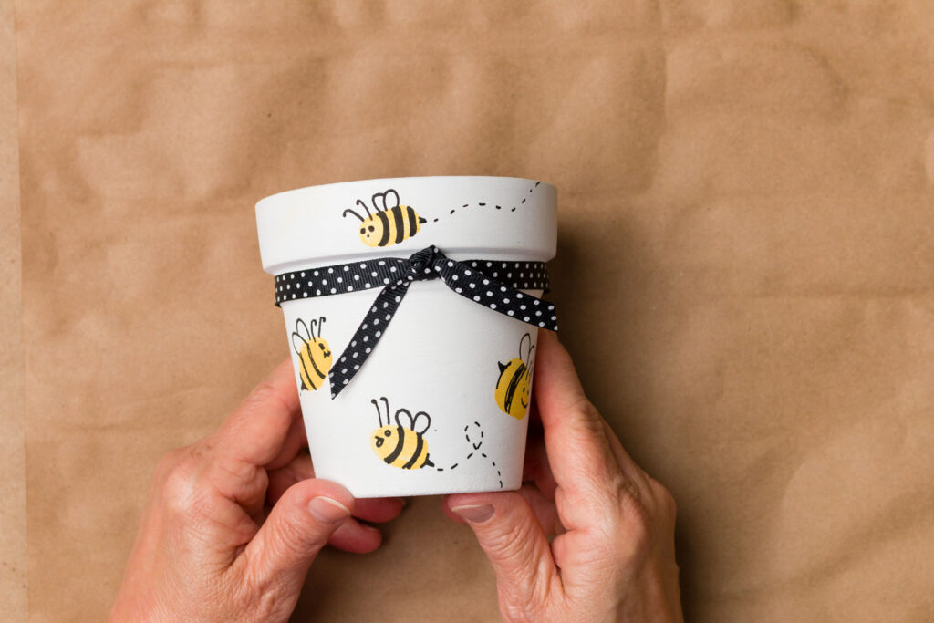 Finished painted pot with bees and polka dot ribbon