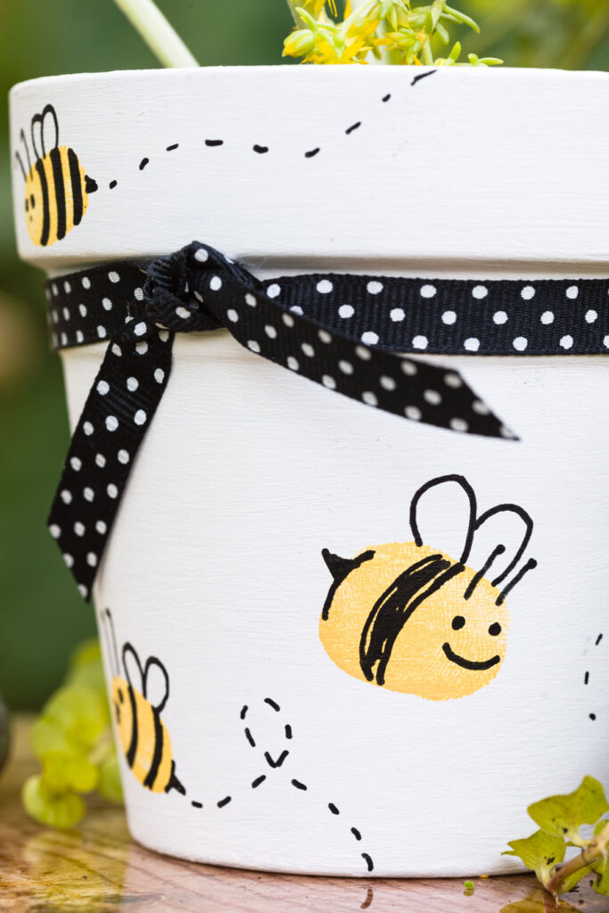 Flower pot painted pot with bees and ribbon in the garden
