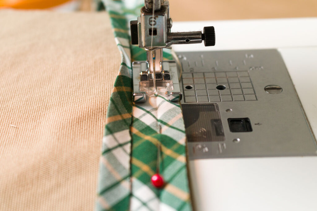 Sew the bias tape to the top edge of the pocket