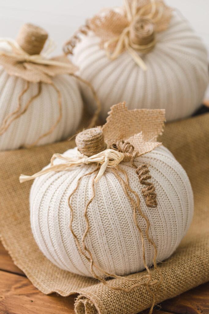 three off white sweater pumpkins sitting on burlap